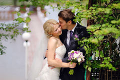 Bride and groom kissing in the park happy Royalty Free Stock Photography