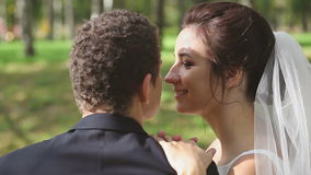 Bride and Groom are Kissing in Park. Wedding Couple Bride and Groom are Kissing on a Wedding Walk Outdoors in Park stock footage