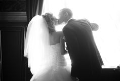 Bride and groom kissing passionately against big window Royalty Free Stock Photo