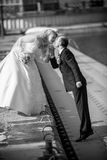Bride and groom kissing on pier at sunny day Stock Photos