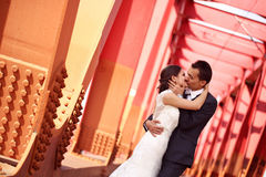 Bride and groom kissing on a red bridge Stock Photos