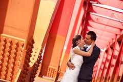 Bride and groom kissing on a red bridge Stock Photo