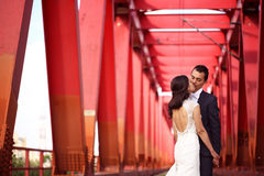 Bride and groom kissing on a red bridge Stock Photography