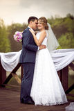 Bride and groom kissing on river pier at sunny day Royalty Free Stock Photo