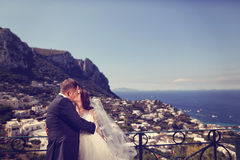 Bride and groom kissing with sea scape in background Royalty Free Stock Images