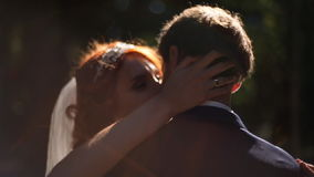 Bride and groom are kissing in a sunny park alley. stock video footage