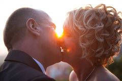 Bride and groom kissing at sunset Royalty Free Stock Photo