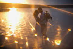 Bride and Groom, Kissing at Sunset on a Beautiful Beach Stock Photography