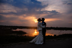 Bride and Groom kissing at Sunset  beautiful Romantic Married Couple Royalty Free Stock Photography