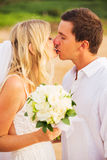 Bride and Groom, Kissing at Sunset on a Beautiful Tropical Beach Royalty Free Stock Photography