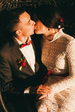 Bride and groom kissing at sunset in chair Stock Photography