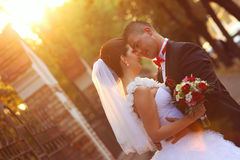 Bride and groom kissing at sunset with a flower bouquet Royalty Free Stock Images