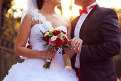 Bride and groom kissing at sunset with a flower bouquet Stock Image