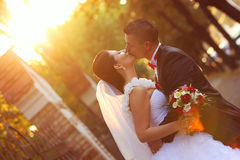 Bride and groom kissing at sunset with a flower bouquet Royalty Free Stock Photo