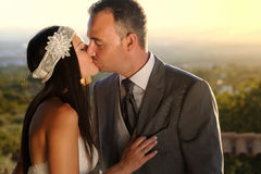 Bride and groom kissing at sunset at a viewpoint Stock Image