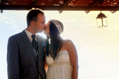 Bride and groom kissing under a porch at sunset Royalty Free Stock Image