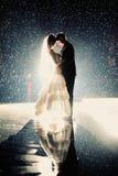 Bride and groom kissing under rain