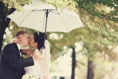 Bride and groom kissing under umbrella Stock Photo