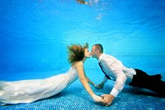 The bride and groom kissing underwater at the bottom of the pool. The bride and groom in wedding dresses kissing underwater at the bottom of the pool. Horizontal Stock Photos