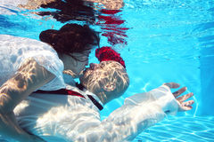 Bride and groom kissing underwater dive pool water rose Royalty Free Stock Photos