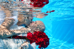 Bride and groom kissing underwater dive pool water rose Stock Image