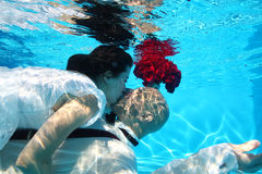 Bride and groom kissing underwater dive pool water rose Stock Photos
