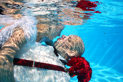 Bride and groom kissing underwater dive pool water rose Royalty Free Stock Image