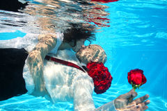Bride and groom kissing underwater dive pool water rose Royalty Free Stock Photography