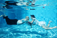 Bride and groom kissing underwater wedding diving red flowers Stock Photos