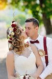 Bride and groom kissing on a walk in the park Stock Image