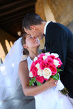Bride and Groom Kissing at Wedding. A beautiful woman bride and handsome man groom kissing at church during wedding stock image