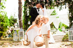 Bride and groom kissing. Bride and groom are kissing after wedding ceremony. Adorable children with flying rose petals in baskets Stock Photo