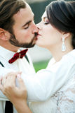 Bride and groom kissing. Wedding couple, newlyweds kiss. Close portrait. The man in bow tie with suspenders. Bride and groom kissing. Wedding couple, bride and Stock Photos