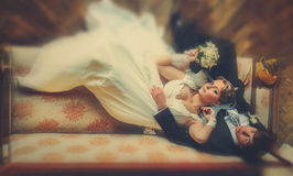 Bride and groom lay carelessly on the old sofa. A Stock Photos