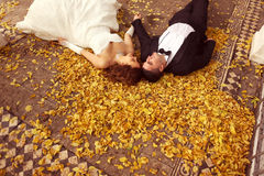Bride and groom laying on autumn leaves Stock Images