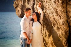 Bride and groom lean against rock Stock Photography