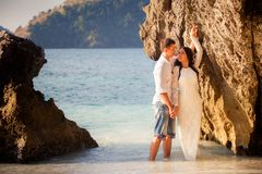 Bride and groom lean against rock Stock Image