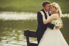 Bride and groom lean to each other standing behind a bench on th. E lake's shore Stock Photos