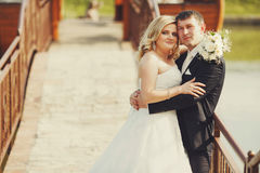 Bride and groom lean to each other standing behind a bench on th Stock Photos