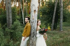 Bride and groom lean on the tree from different sides. Newlyweds are walking in the forest. Artwork.  Stock Photography