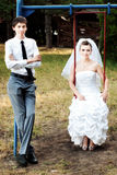 Bride and groom leaning on swings Stock Photography