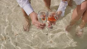 The bride and groom let out two fishes from glass bowls in ocean. Wedding idea. The symbol of the pair. Exotic beach. The bride and groom let out two fishes stock video