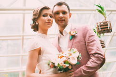 Bride and groom in light hothouse. Happy bride and groom in light hothouse stock photos
