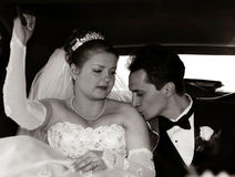 Bride and Groom in the limo. Groom kissing the bride in a limo stock photo