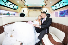 Bride and groom in limousine Stock Photos