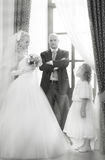 Bride and groom and little girl at a wedding Stock Images