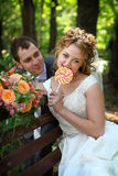 Bride and groom with lollypop. Bride and groom in park eating lollypop together Stock Image