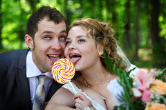 Bride and groom with lollypop Royalty Free Stock Photos