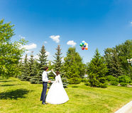 Bride and groom look balloon in blue sky Royalty Free Stock Images