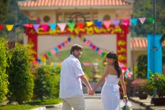 Bride and groom look at the camera, leaving the summer Park outdoors, holding hands royalty free stock photo